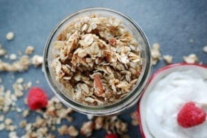Almond coconut granola in a small jar. Granola and raspberries sprinkled around the jar on the counter with greek yogurt.