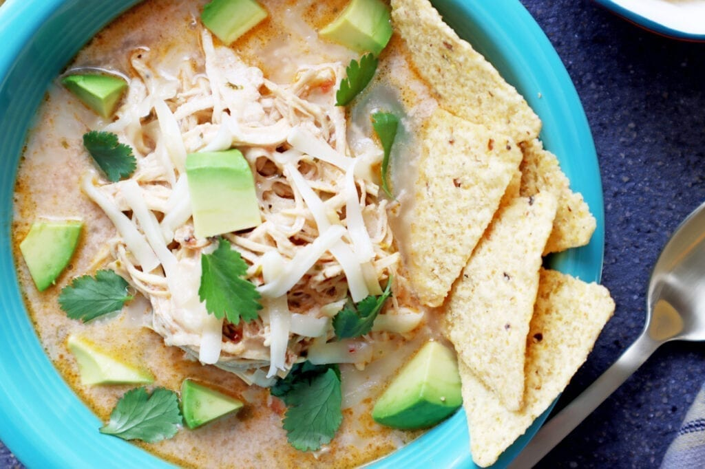 Instant Pot Chicken Tortilla Soup in a teal bowl with tortilla chips on the side. Cheese cilantro sour cream on the side with a spoon next to the bowl.