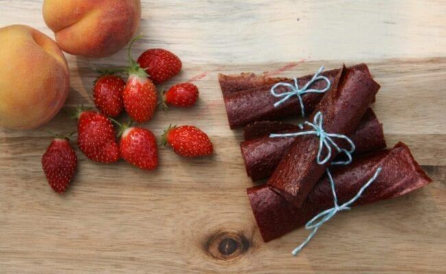Strawberry peach fruit leather rolled up and tied with blue string with fresh peaches and strawberries on a wooden cutting board.