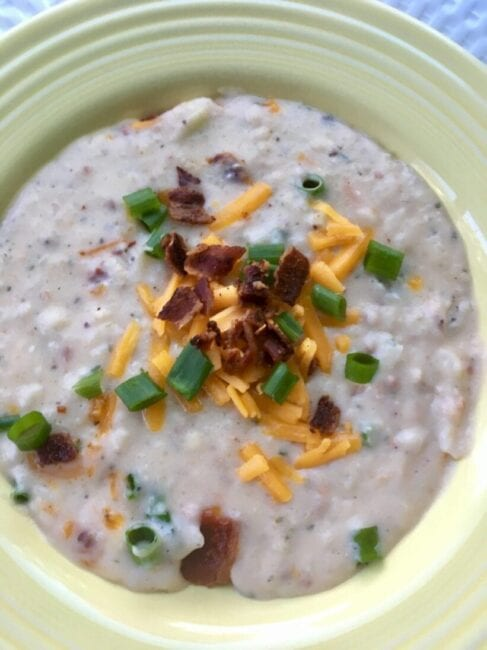 Potato Soup with cheddar cheese green onion and bacon on top in a light yellow bowl