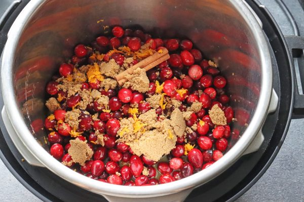 Instant Pot Cranberry Sauce Recipe from Scratch with fresh cranberries, orange juice, cinnamon stick, orange zest, brown sugar and maple syrup in the instant pot