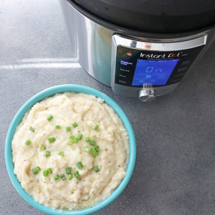 Easy Instant Pot mashed potatoes. Thanksgiving side dish. Butter, milk, green onions, garlic served in a teal bowl.