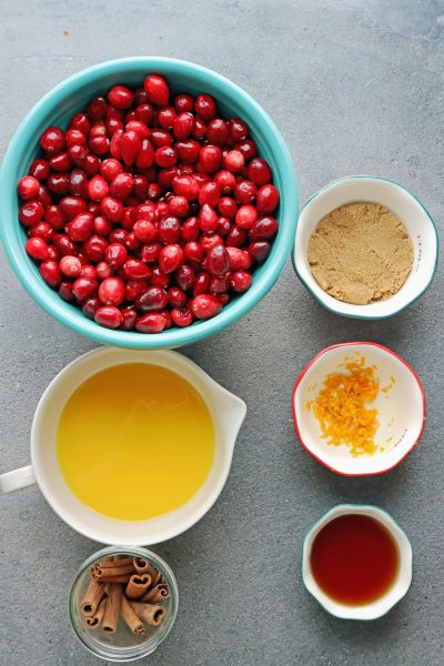 Instant Pot Cranberry Sauce Recipe from Scratch with fresh cranberries, orange juice, cinnamon stick, orange zest, brown sugar and maple syrup. In bowls on the counter.