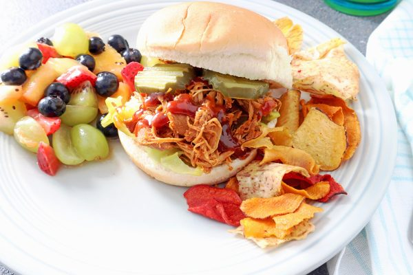 Instant Pot BBQ chicken recipes on a potato bun with veggie chips and fruit salad on the side on a grey plate