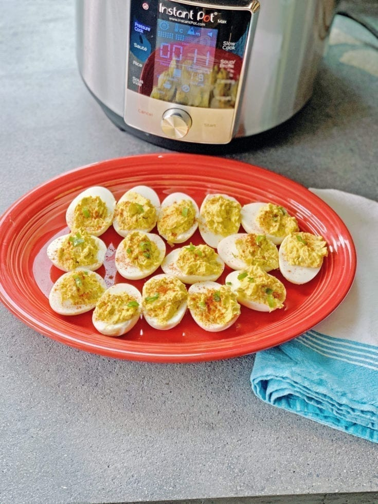 Instant Pot Deviled eggs on a red platter sitting next to the instant pot and a teal and white towel