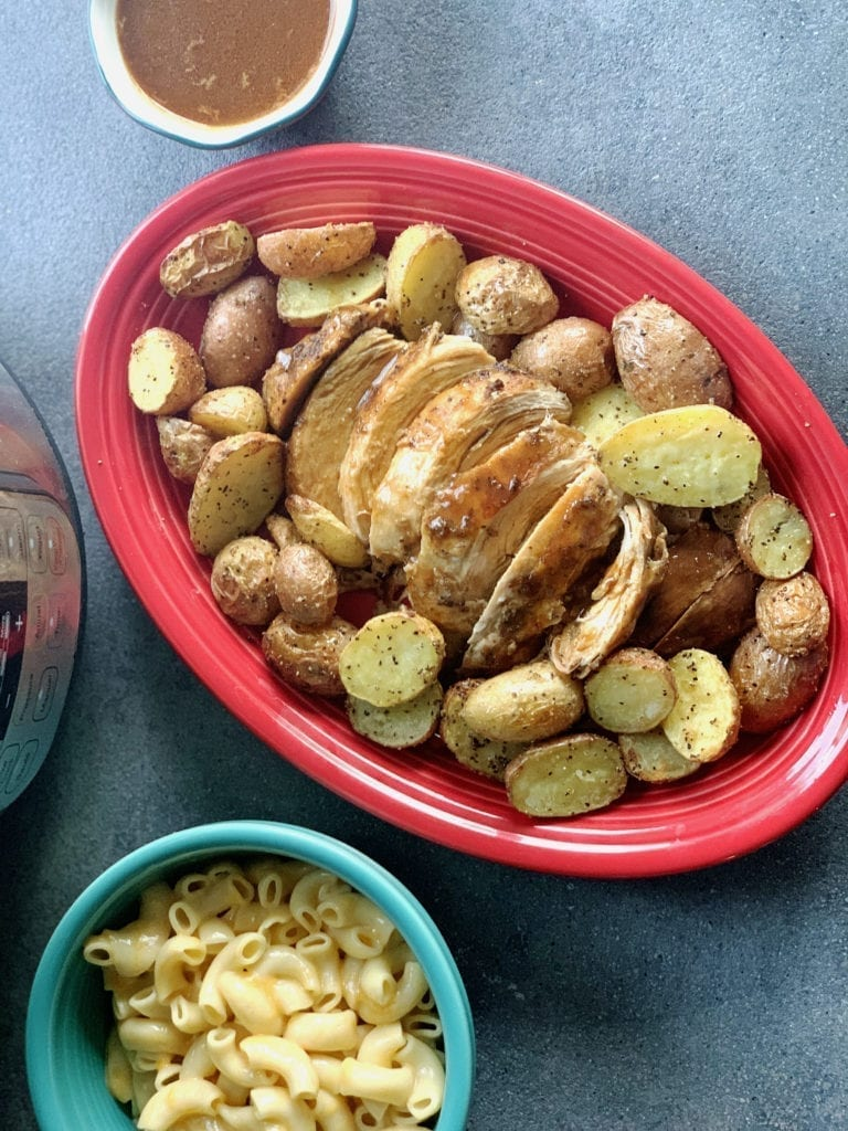Instant Pot Cajun Turkey Breast & roasted potatoes on a red platter with mac & cheese on the side.