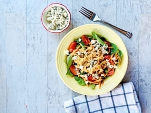 Buffalo chicken salad in a yellow bowl with a fork and blue cheese crumbles, a fork and a blue and white towel on the side.