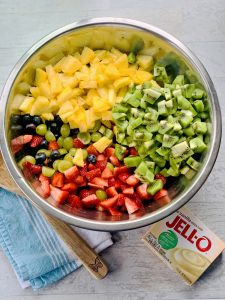 Easy Vanilla Fruit Salad Recipe with pineapple, strawberries, green grapes, blueberries, kiwi and vanilla jello pudding mix in a large silver bowl.