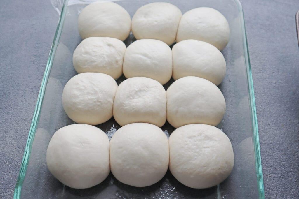 Rising bread dough for cheese stuffed garlic knots in a glass baking dish