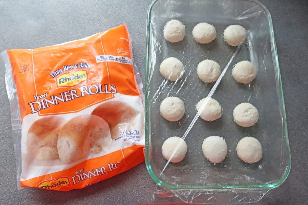 Package of frozen dinner rolls next to Rising bread dough for cheese stuffed garlic knots covered with plastic wrap