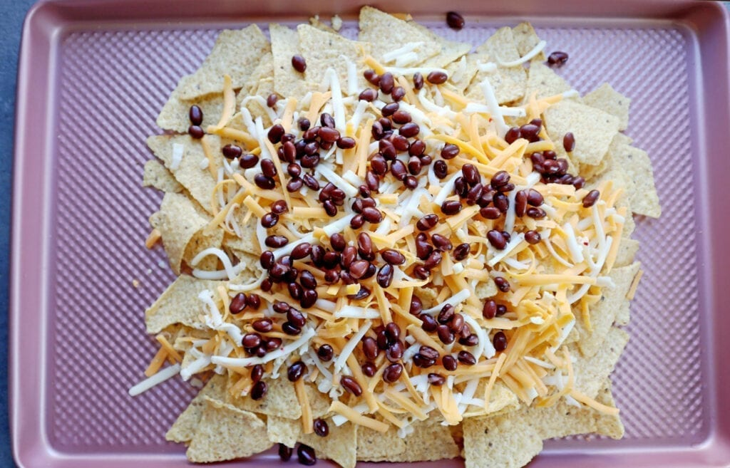 Instant Pot Dr. pepper pork nachos with tortilla chips, cheese, black beans on a pink baking sheet.