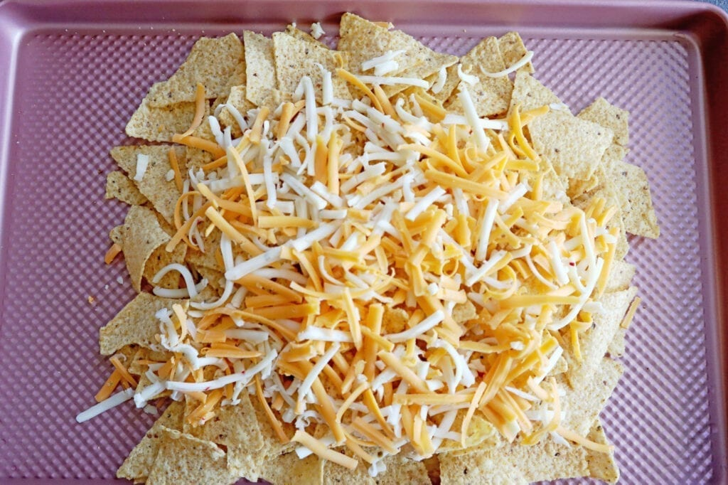Instant Pot Dr. pepper pork nachos with tortilla chips & cheese, on a pink baking sheet.