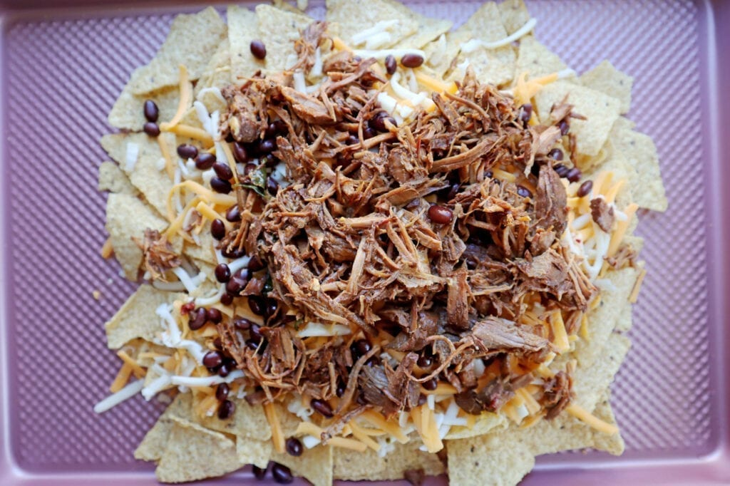 Instant Pot Dr. pepper pork nachos with tortilla chips, cheese, black beans and shredded Dr. Pepper Pork on a pink baking sheet.