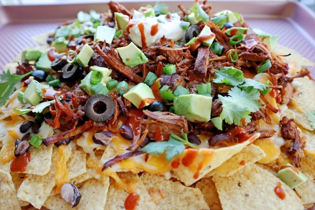 Dr Pepper pork nachos on tortilla chips with cheese, olives, sour cream, avocado & hot sauce