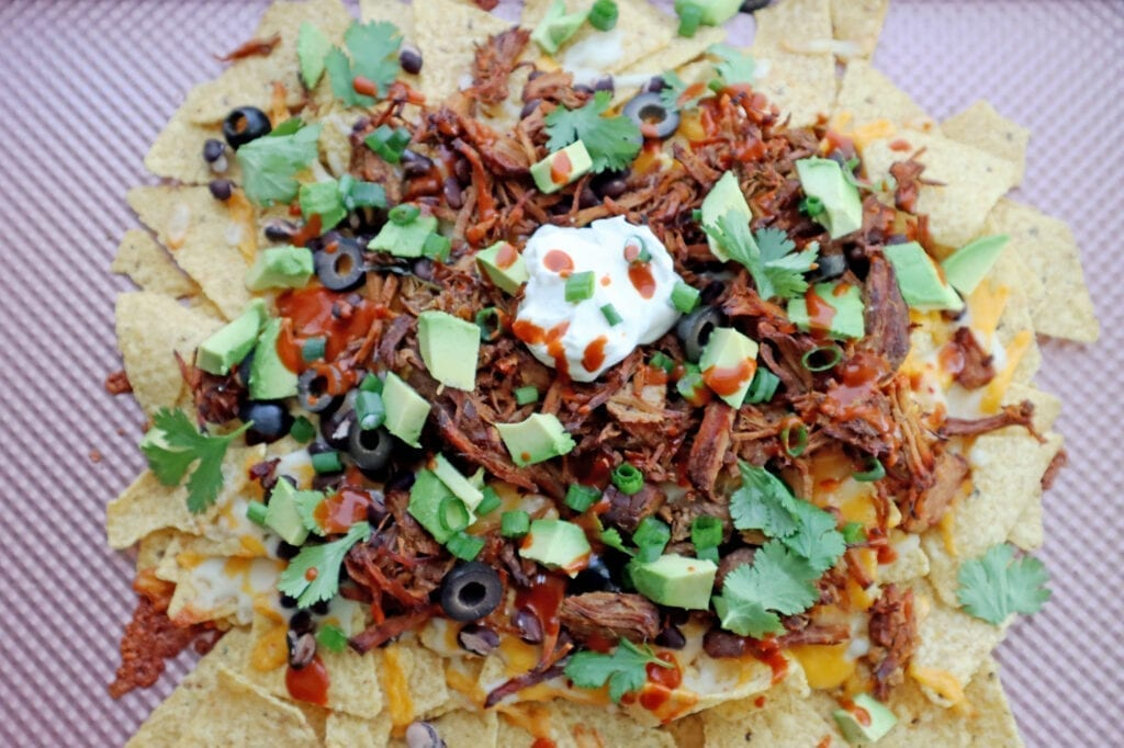 Instant Pot Dr. pepper pork nachos with tortilla chips, cheese, black beans and shredded Dr. Pepper Pork toped with avocado, black olives, sour cream and hot sauce on a pink baking sheet.