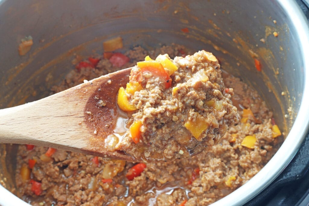 Cooked Instant Pot Sloppy joes ground sauteing hamburger, bell peppers and onions on a wooden spoon