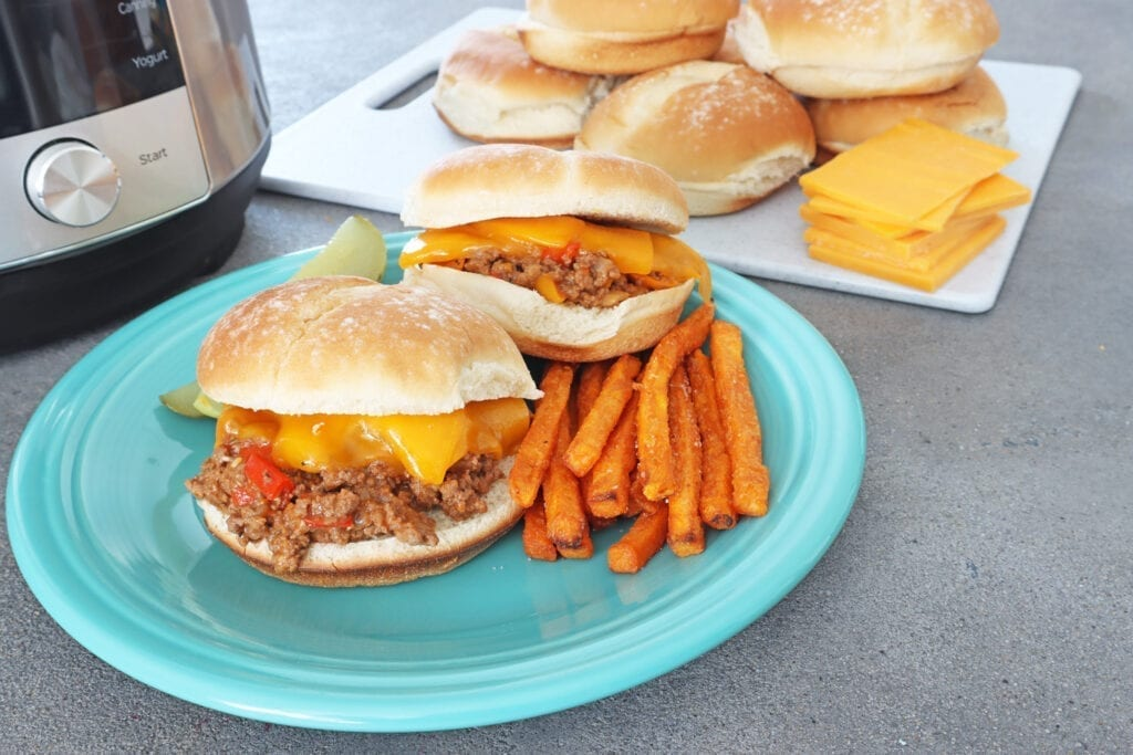 Instant Pot Sloppy Joes on a teal plate with sweet potato fries with buns and cheese