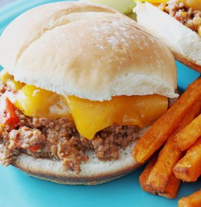 Instant Pot Sloppy Joes recipe with sweet potato fries and pickles on the side on a blue plate