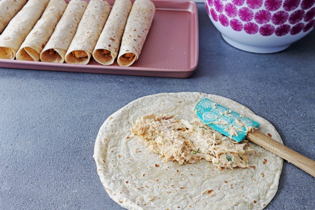 Air fried chicken flautas ingredients on a whole wheat tortilla