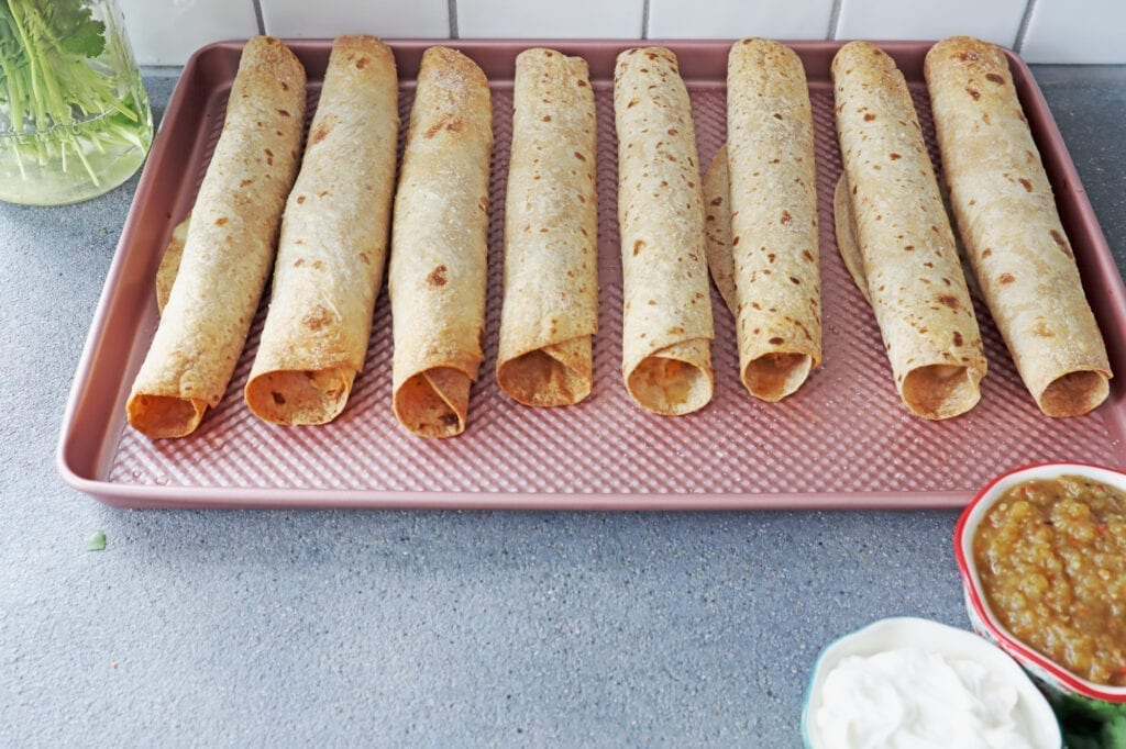 Air fried chicken flautas ingredients rolled up into whole wheat tortilla. Brushing with EVOO and sprinkling with salt