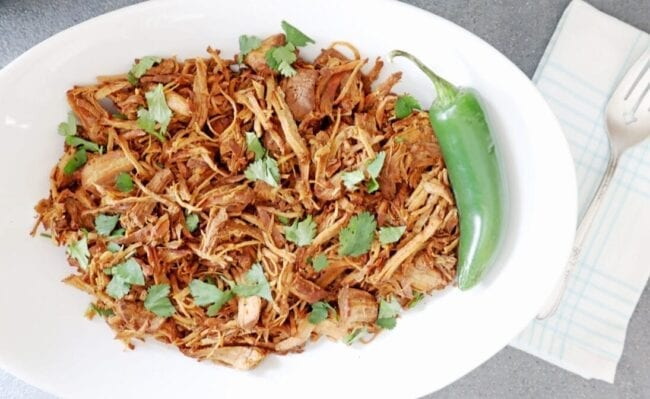 Shredded Dr Pepper pork in a white bowl with a jalapeno and cilantro on top