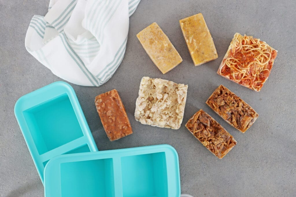 Teal Souper Cube trays with frozen food cubs and white towel on the counter