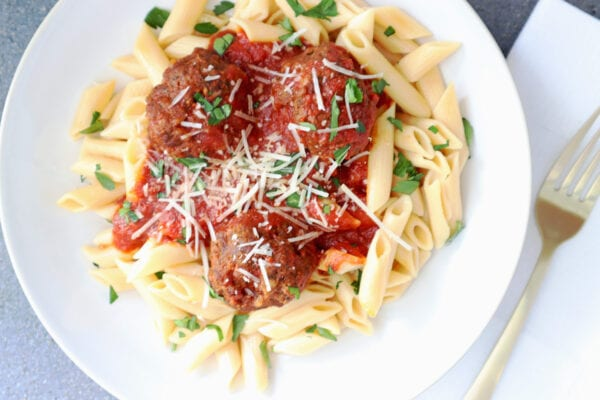 Instant Pot Banza chickpea pasta with meatballs and marinara sauce in a white bowl with a gold fork and white napkin