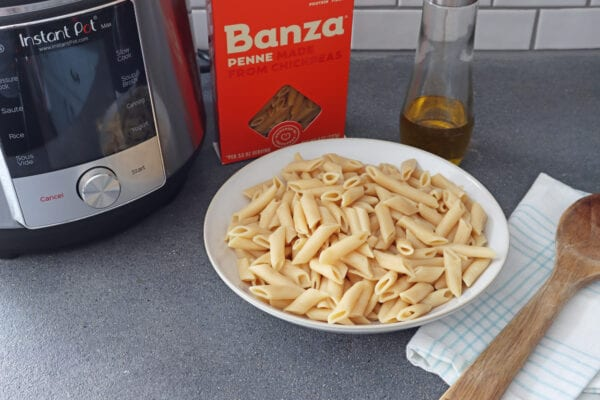 Banza chickpea pasta in a white bowl next to olive oil, a box of pasta and instant pot