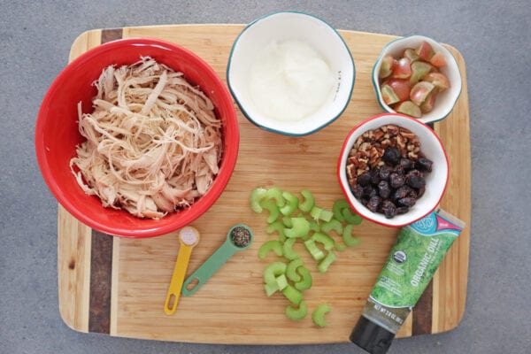 Instant Pot Chicken Salad ingredients, shredded chicken, greek yogurt, red grapes, celery, spices, nuts and dried cranberries & dill on a wood cutting board