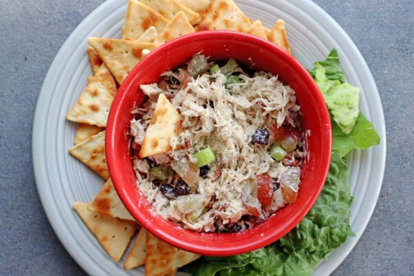 Instant Pot Chicken Salad Recipe in a red bowl with pita chips and lettuce on the side on a grey plate