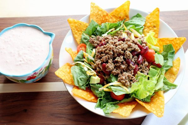 Doritos Taco Salad with ground beef, red beans, cherry tomatoes, & cheese on romaine lettuce in a white bowl. Creamy salsa dressing in a cup on the side.