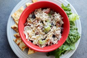 Healthy Instant Pot Chicken Salad recipe with grapes, celery, dried cranberries, greek yogurt in a red bowl with crackers and lettuce on the side