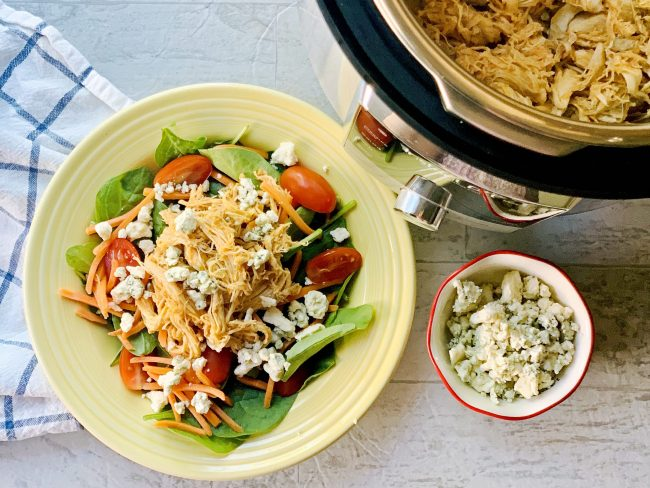 Instant Pot Buffalo chicken salad on yellow plate next to Instant pot and blue cheese crumbles and white and blue towel
