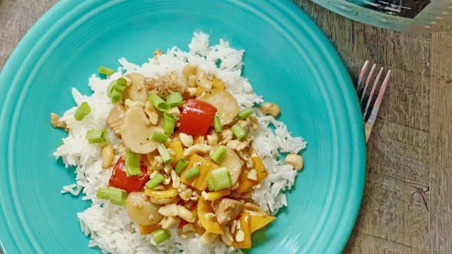 Instant Pot cashew chicken recipes on a teal plate next to a blue and white towel