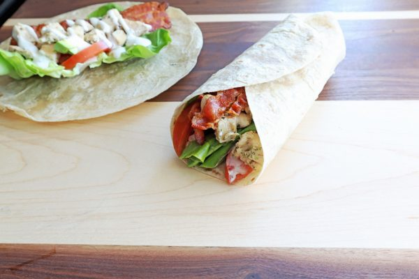 whole wheat tortilla with tomato, lettuce, chicken and ranch on a wood board