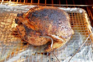 Frigidaire Air Fry Range Air Fryer Whole Chicken on a wire rack with meat thermometer sticking out of the leg.