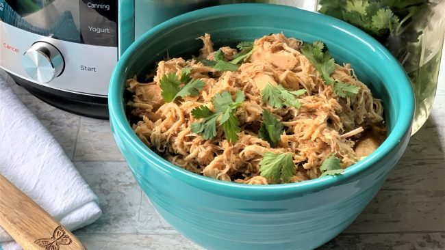 Instant Pot Chicken Taco meat in a teal bowl with cilantro on top. Next to an instant pot