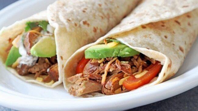 Dr Pepper Pork Burrito recipe. Two Burritos topped with tomato and avocado on a white plate