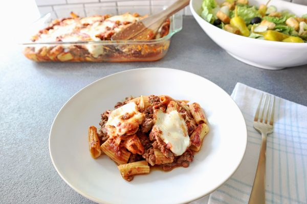 Banza Chickpea Pasta Bake. Italian sausage, rotini, parmesan, mozzarella, baked in the oven. Pasta in a white bowl with salad on the side.