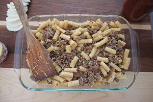 Banza Chickpea Pasta Bake. Italian sausage, rotini, parmesan, mozzarella layered in a glass baking dish with a wooden spatula.