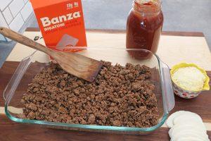 Banza Chickpea Pasta Bake. Italian sausage, rotini, parmesan, mozzarella layered in a glass baking dish. Pint jar of marinara sauce on the side.