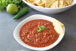 5 minute blender salsa in a white bowl with tortilla chips fresh jalapeno limes and cilantro on the side.