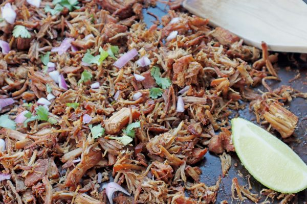 Instant Pot Crispy pork Carnitas shredded on a baking sheet to crisp up the meat with fresh cilantro and purple onion on top.