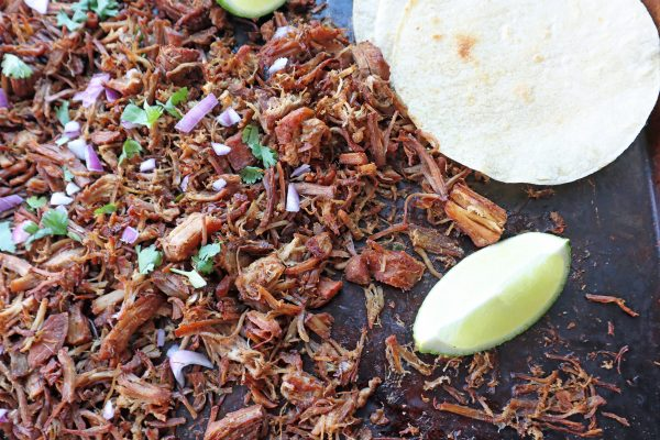 Instant Pot Crispy pork Carnitas shredded on a baking sheet to crisp up the meat with fresh cilantro and purple onion on top. Flour tortillas and fresh lime wedge on the side.