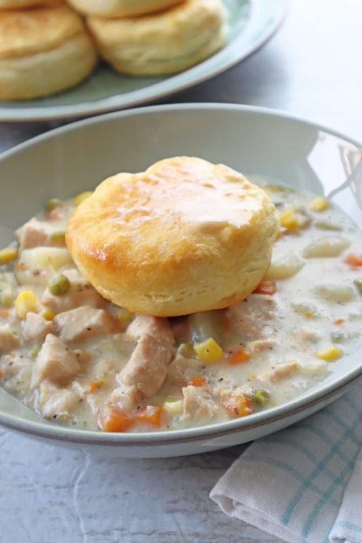 Easy Instant Pot Chicken Pot Pie with biscuits in a green bowl.